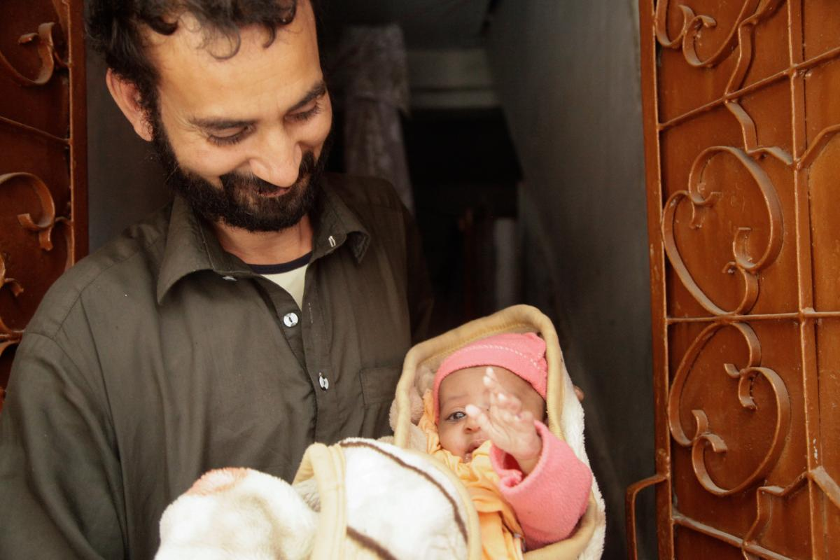 A father holds his son, who was vaccinated two days earlier, as the health workers who'd administered the vaccine return for a follow-up check.