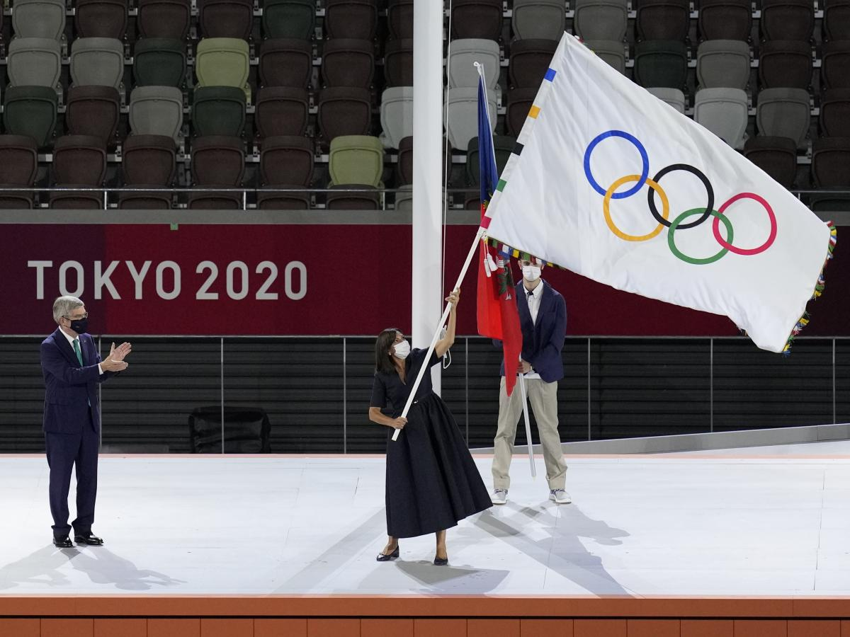 Paris mayor Anne Hidalgo, right, holds the Olympic flag during the closing ceremony in the Olympic Stadium at the 2020 Summer Olympics, Sunday, Aug. 8, 2021, in Tokyo, Japan.