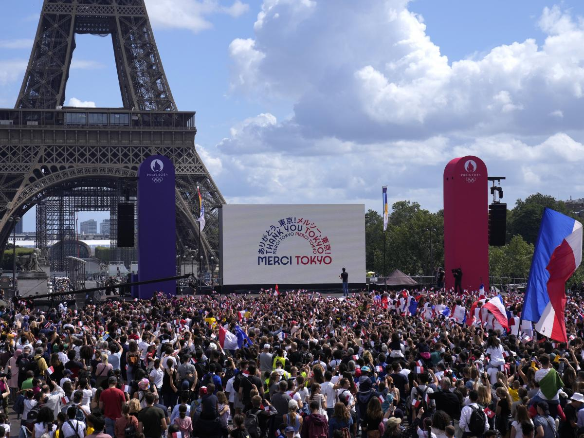 Spectators gather by the Eiffel Tower in Paris as part of the handover ceremony during the closing ceremony of the Tokyo Olympic games.