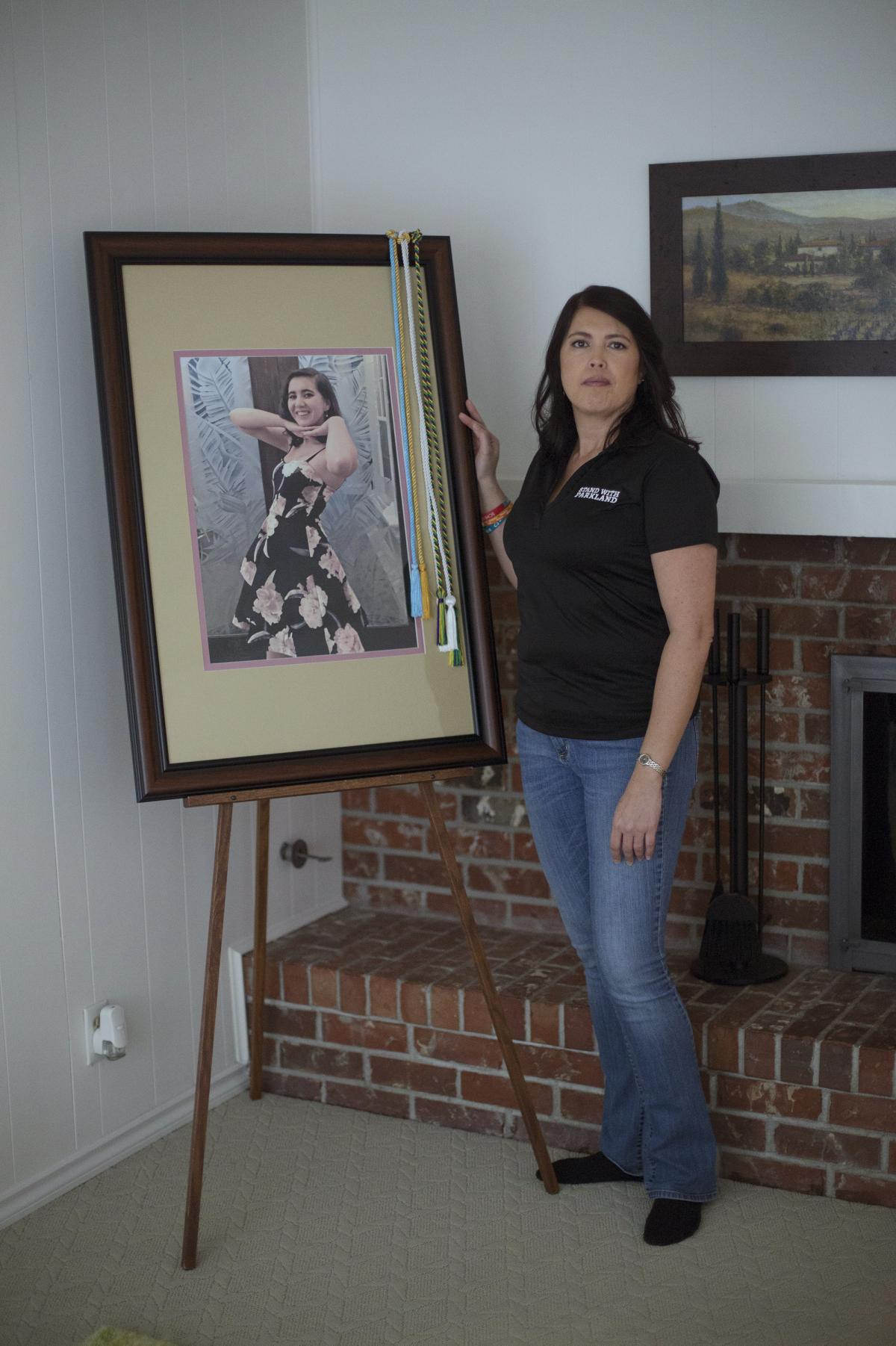 One year after Carmen's death, April Schentrup stands beside a photograph of her daughter that was used during her funeral but now rests in the family's new home. April, who worked as an elementary school principal in Parkland, Fla., now advocates for gun