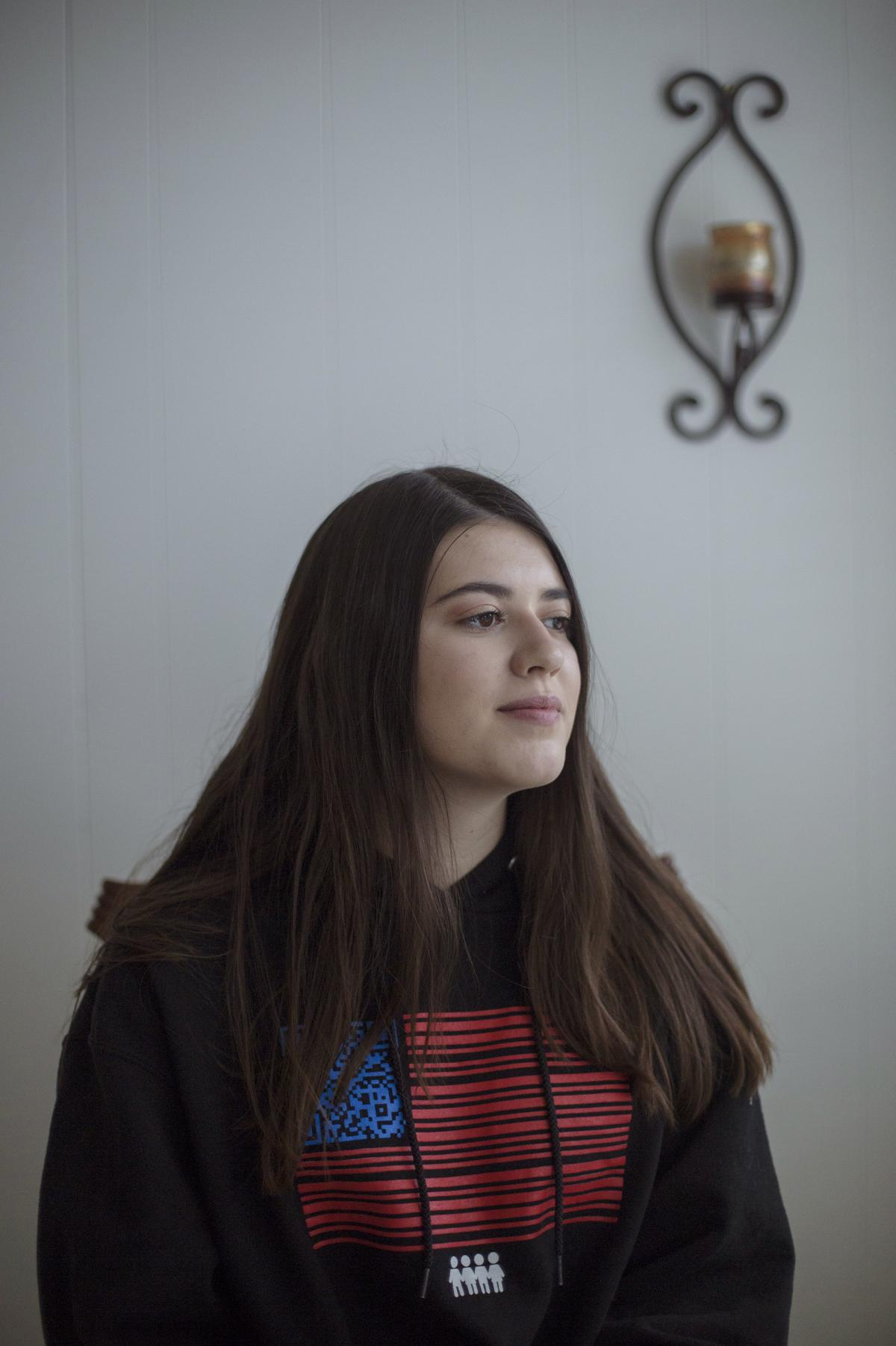 Evelyn Schentrup wears a sweatshirt designed by students involved with the March for Our Lives organization. Since the shooting and moving with her family across the country, Evelyn has struggled with anxiety and enrolled in online high school classes.