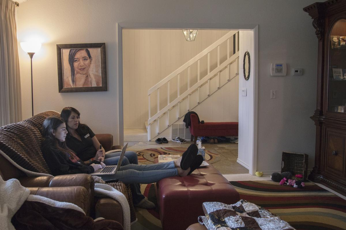 """Evelyn and April sit below a portrait of Carmen. The painting, acrylic on canvas, is by Parkland artist Nava Lundy, who created portraits of all 17 Parkland victims and gave them to the families. """"I just felt this urgency,"""" Lundy says. """"I felt like I had"""