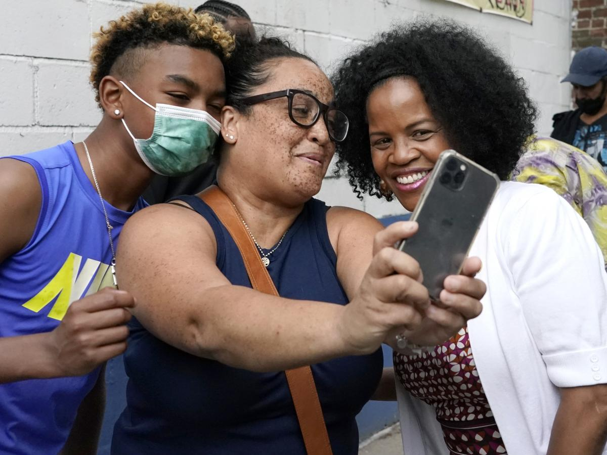 Acting Mayor Kim Janey, right, takes a photo as Bostonians gather together on Friday in Nubian Square. Janey is the first woman and first Black person to serve as mayor of Boston.