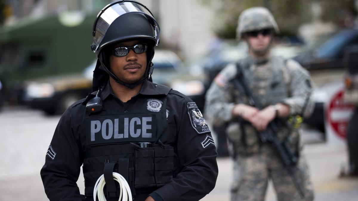 A National Guardsman and a police officer hold their positions at City Hall during a protest Wednesday in downtown Baltimore. Thousands marched, demanding justice for an African-American man who died of severe spinal injuries allegedly sustained in police