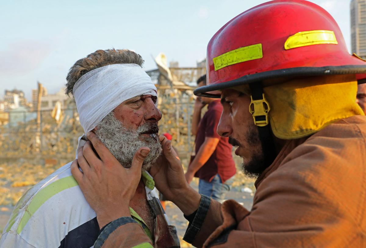 A firefighter checks a wounded man near the scene of the explosion in Beirut.