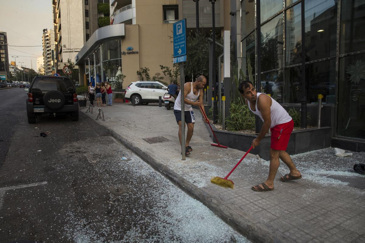 Residents sweep glass off the sidewalk after the large explosion in Beirut. Images from the scene show that entire blocks of buildings were wrecked along the port, their structural supports crumpled by the blast. Numerous fires broke out, sending black sm