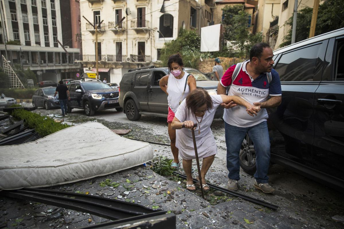 A woman is assisted while walking through debris after Tuesday's explosion in Beirut.