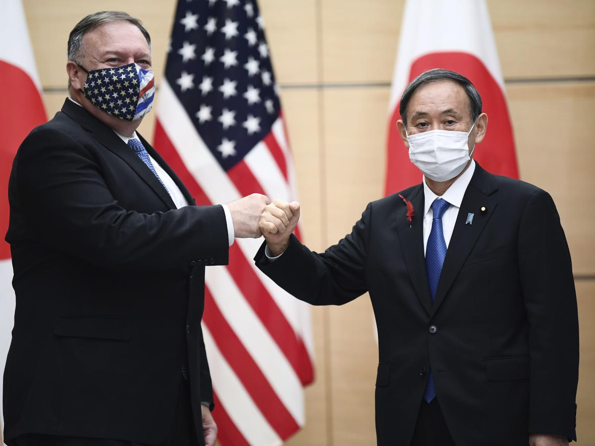 """Pompeo and Japanese Prime Minister Yoshihide Suga greet each other Tuesday in Tokyo ahead of the """"Quad"""" meeting."""