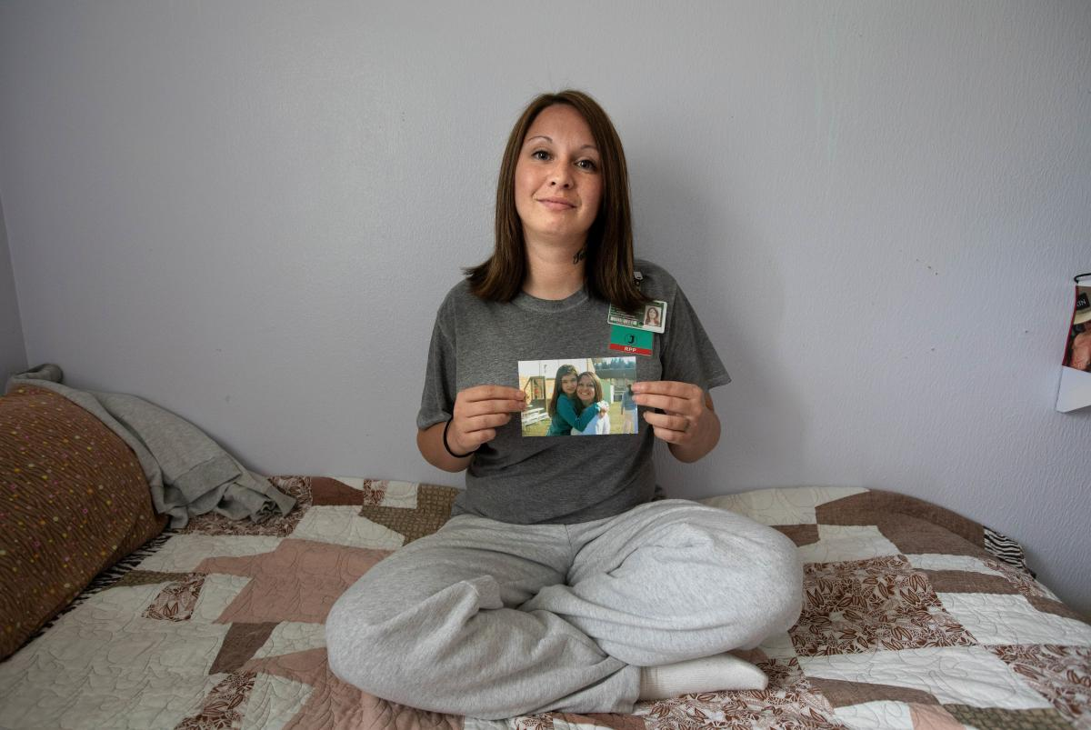 Ashley Templeman holds a photo of her and her now 9-year-old daughter. Part of the parenting program years ago, Templeman relapsed after her release and returned to prison. She's now a caregiver with the program, providing relief for new mothers.