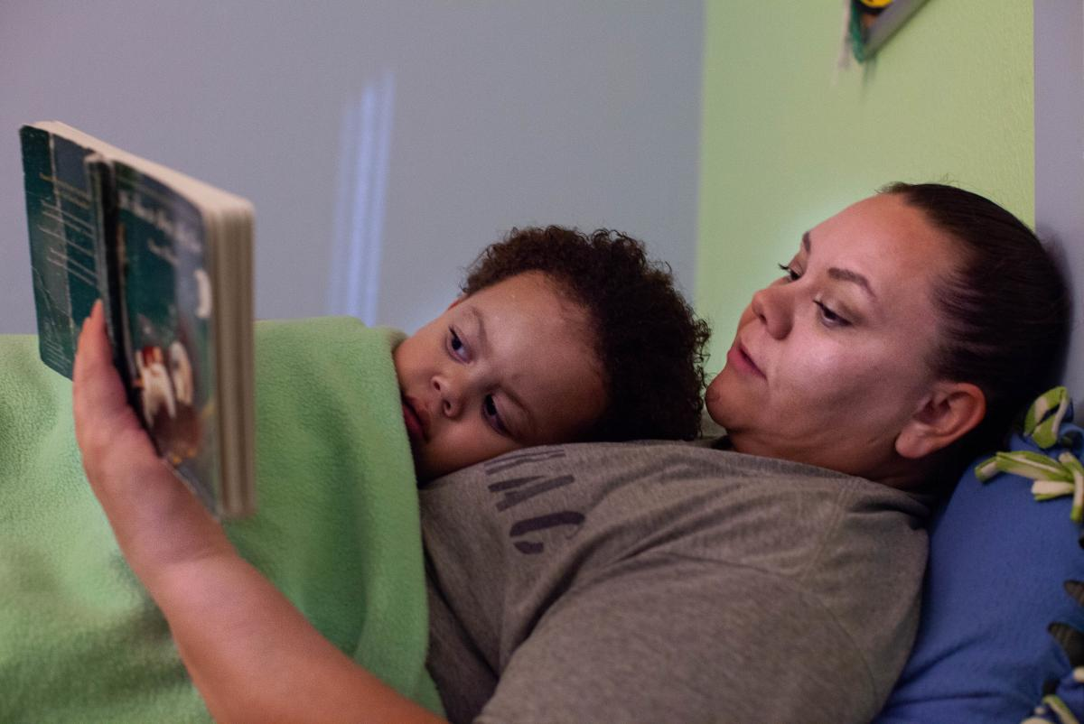 Crystal Lansdale reads to her son, Kirshawn, before bed. Rooms in the Residential Parenting Program are made to look more like a home.