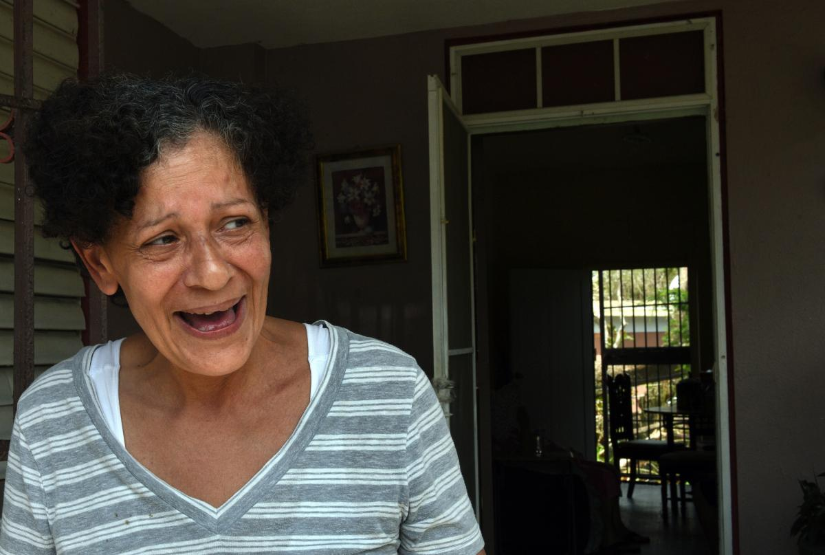 """Daly Montavo, born in Puerto Rico and raised in New York City, laughs at her home on Avenida Esteves after filling jugs of water from a National Guard delivery to the neighborhood. She says, """"We're here and that's all that matters."""""""