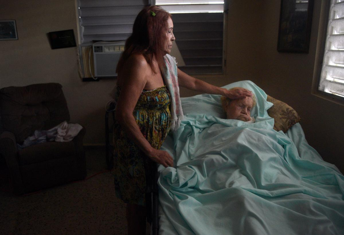 Floodwaters seep into home of 97-year-old Margarita Maestre on Avenida Esteves. She is bedridden with respiratory issues and a feeding tube, with caregiving provided by her daughter Blanco Matos, weary from concerns about her medical needs and the inabili