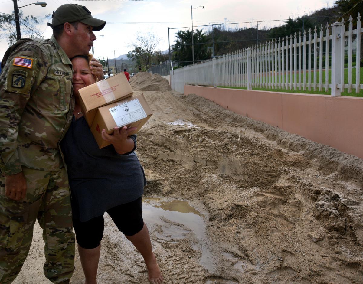 Sgt 1st Class Alejandro Echevarria hugs resident Glenda Montero as National Guard troops deliver aid needed on Avenida Esteves.