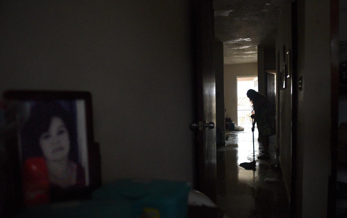 Daughter Blanco Matos mops the floodwaters that seep into home of her mother 97-year-old Margarita Maestre on Avenida Esteves. An old family photo of Margarita sits on a dresser.