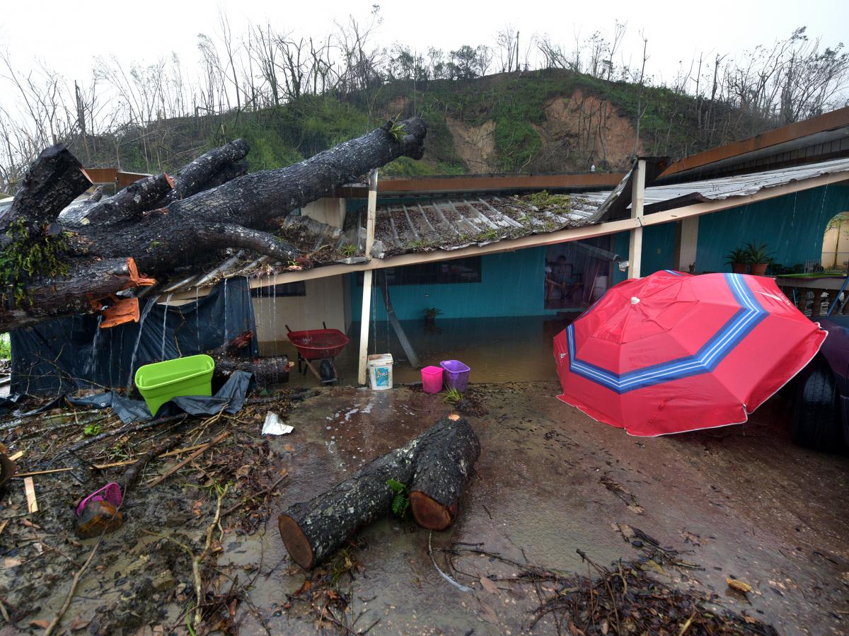 A bridge repair gives out in torrential rain and floodwaters on a street in Utuado.