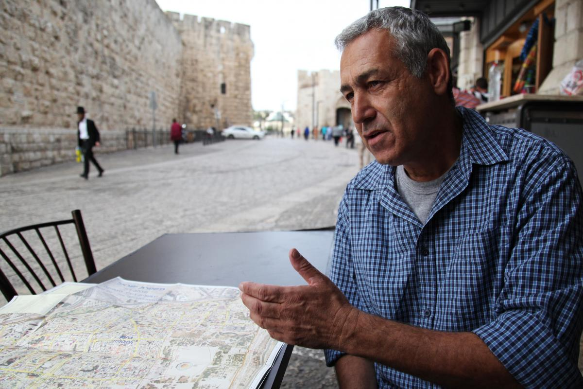 Ami Meitav, a former Israeli intelligence officer and now a tour guide, looks at a map of Jerusalem's Old City as he sits near one of the entrances. He would like to see cameras at the religious site, but believes Muslim religious authorities will oppose