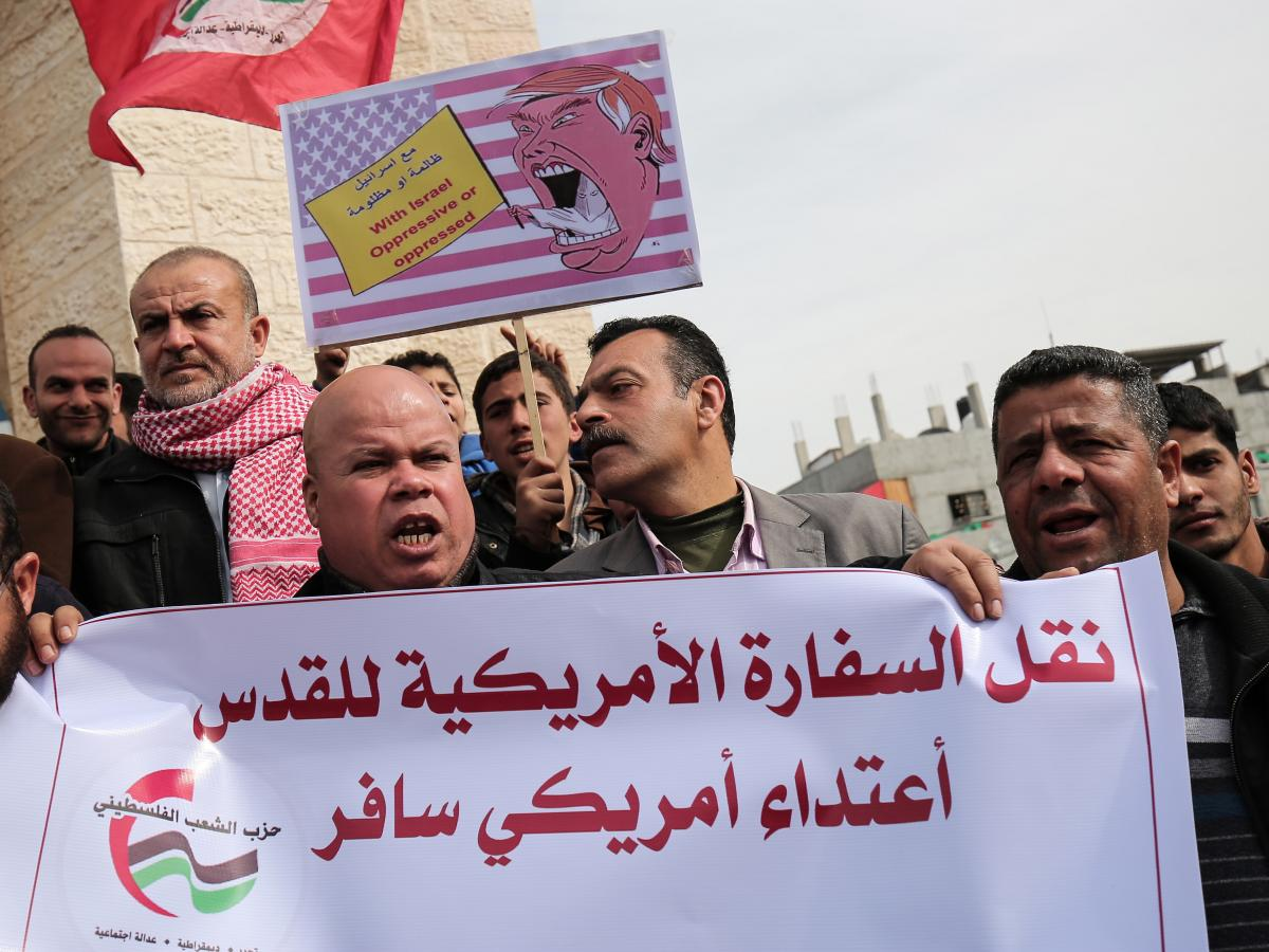"""Palestinian demonstrators protest President Trump's pledge to move the U.S. Embassy to Jerusalem, in Rafah in the southern Gaza Strip in January. The sign in Arabic reads: """"Moving the U.S. Embassy to Jerusalem is a flagrant aggression."""""""