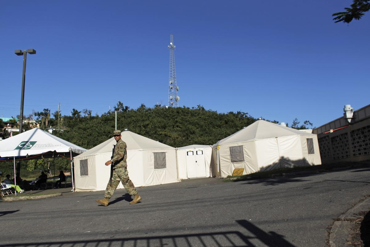 A Puerto Rico National Guard member walks past the health clinic in Vieques, operating out of tents in a parking lot.
