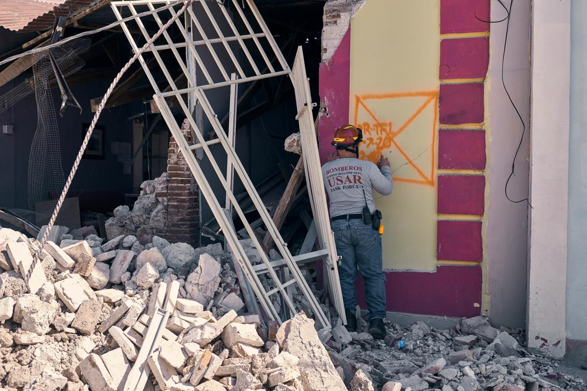 A firefighter searches a building that was severely damaged in Guanica after Tuesday's earthquake.