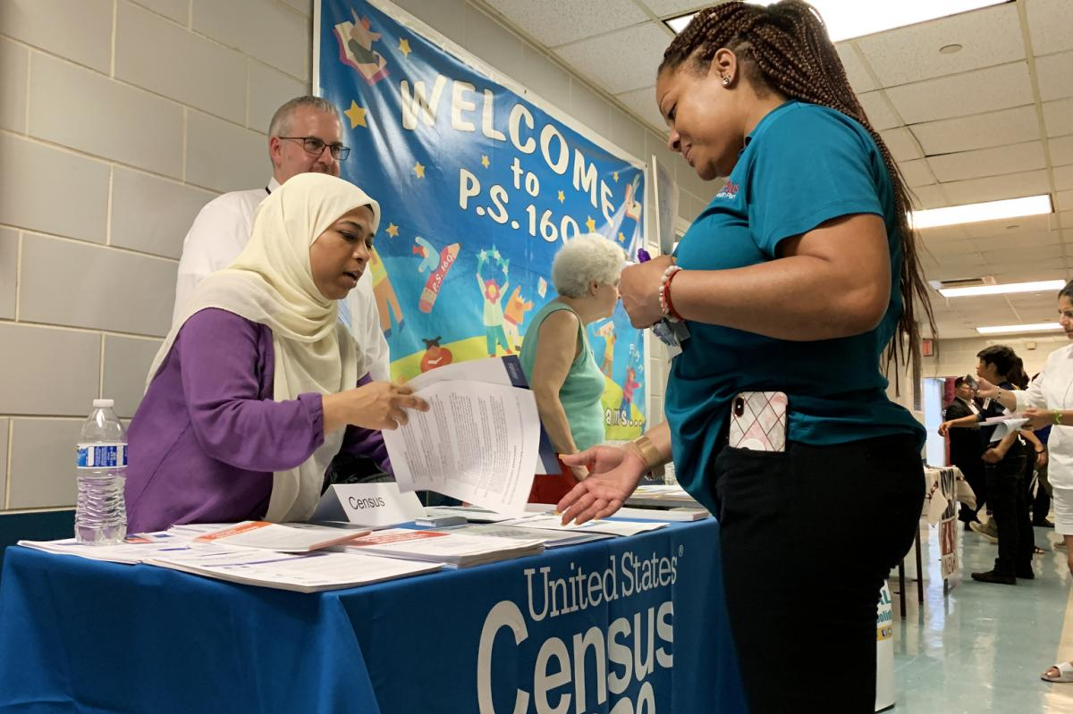 Census Bureau partnership specialist Zakera Ahmed (left) and Jeff Behler, a regional director with the bureau, share information about the 2020 census at an elementary school in Corona, N.Y.