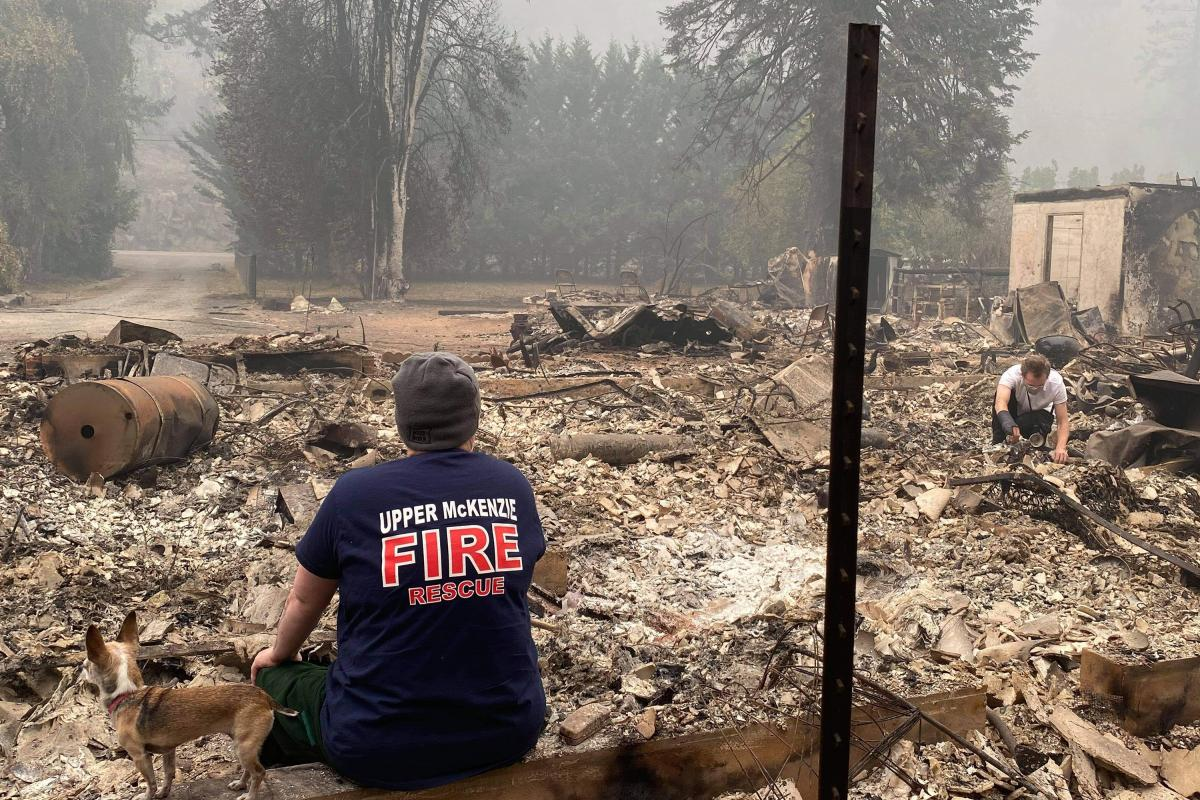 Fire Chief Christiana Rainbow Plews sits in the wreckage of her home, destroyed by the Holiday Farm wildfire in September.