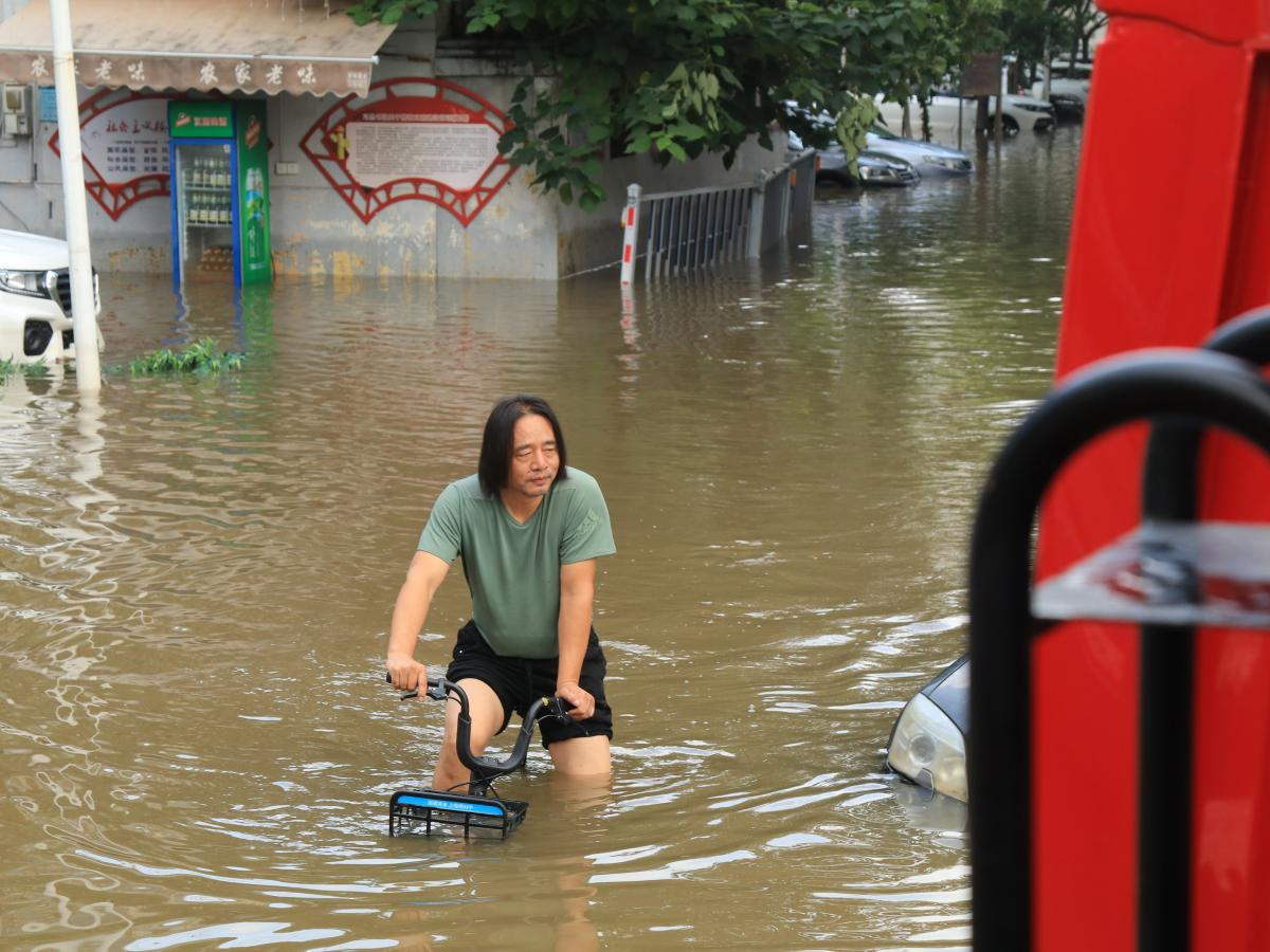 A man rides a bicycle in the flooded streets of Xinxiang.