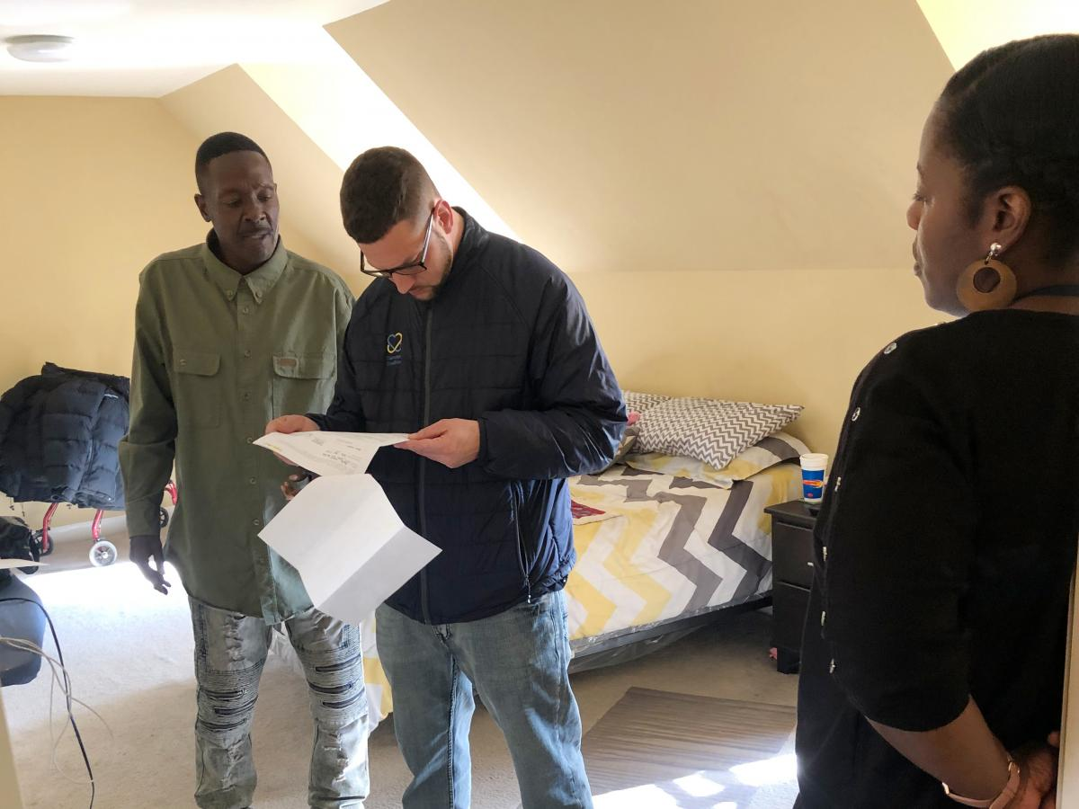 Larry Moore (left) meets with Camden Coalition housing coordinator Brian Thompson and Coalition nurse Jeneen Skinner in his apartment in Camden, N.J. Having a stable housing situation, as well as getting addiction treatment dramatically reduced Moore's tr