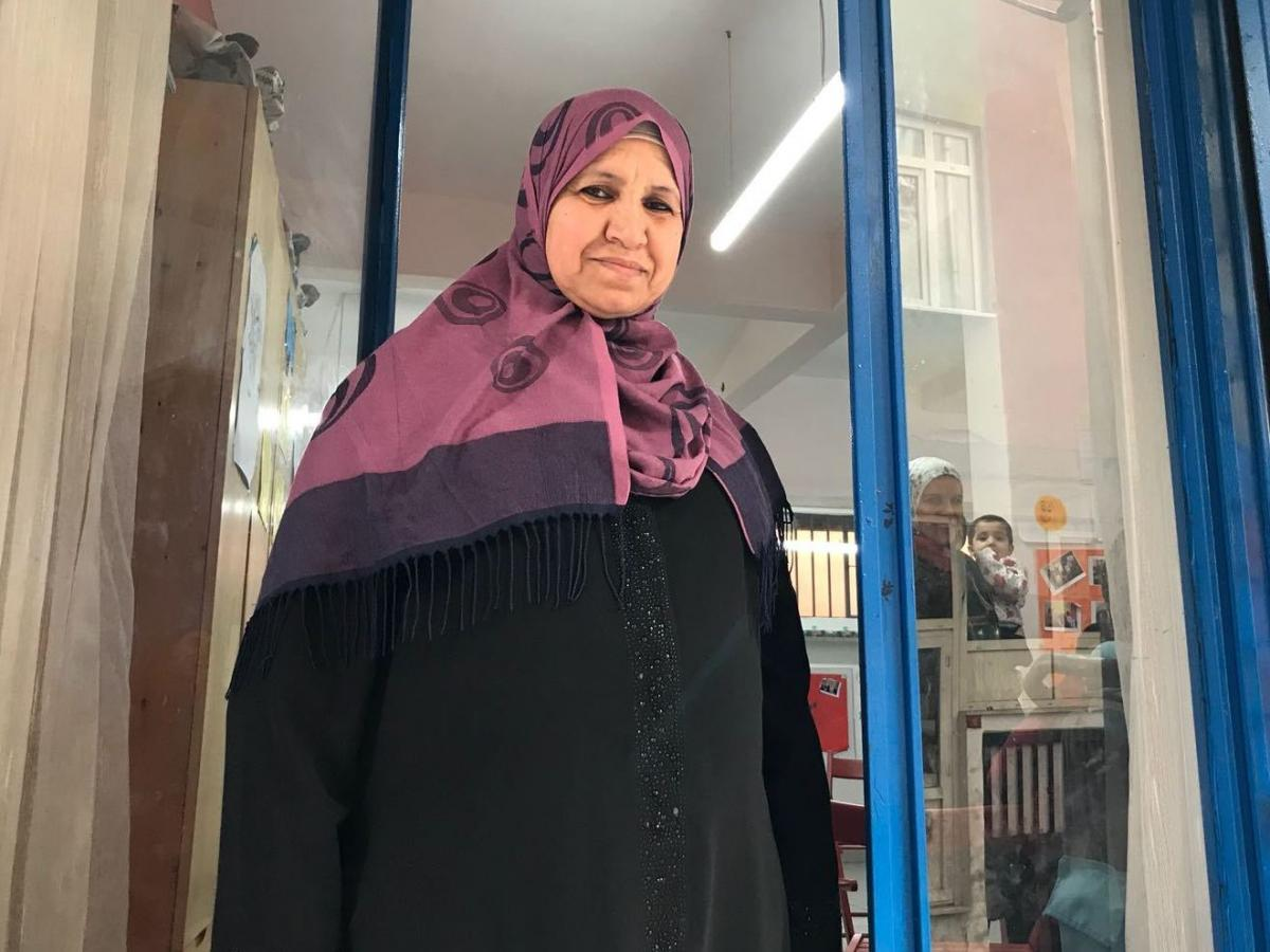"""Maryam Ahmed standing at the entrance to the """"Women's Solidarity Kitchen."""""""
