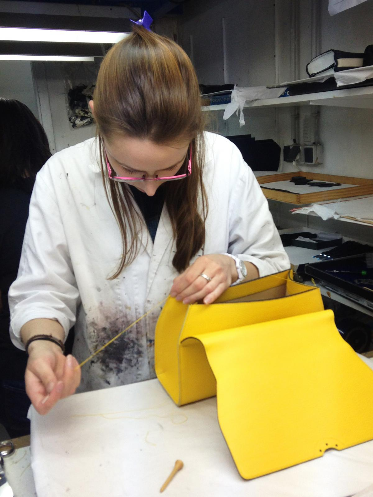 An employee sews a Moynat handbag in an atelier above the company's boutique.