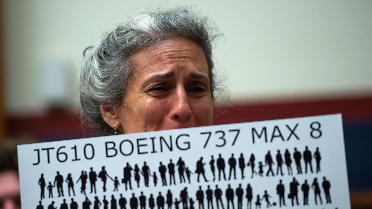 The mother of a victim of the Ethiopian Airlines crash, which killed scores of passengers last year, bears a sign representing the dead passengers before a congressional hearing on the Boeing 737 Max 8 back in June.