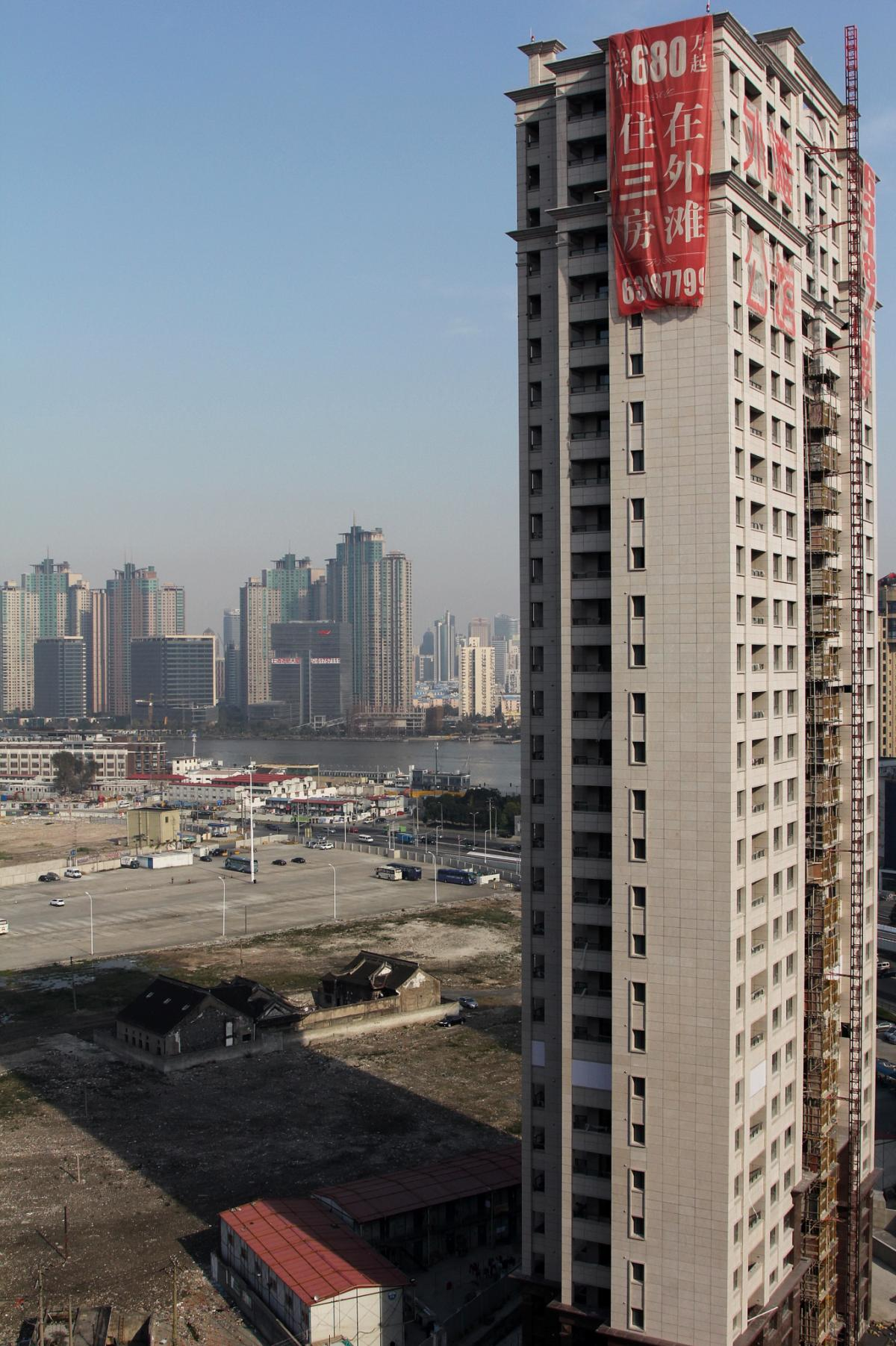 A luxury apartment tower rises near Shanghai's Huangpu River. Chen, an underground Christian who has sent his family to Los Angeles, hopes his home will be knocked down to make way for buildings like this one across the street, so Chen can use the compens