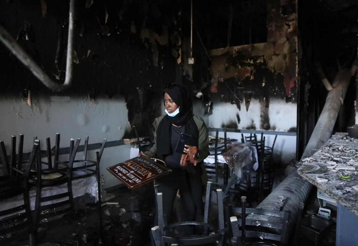 "Saida Hassan looks over the remains of her mother's restaurant, Mama Safia's Kitchen, on Saturday. She doesn't want destruction, but says, ""people are crying for help."""
