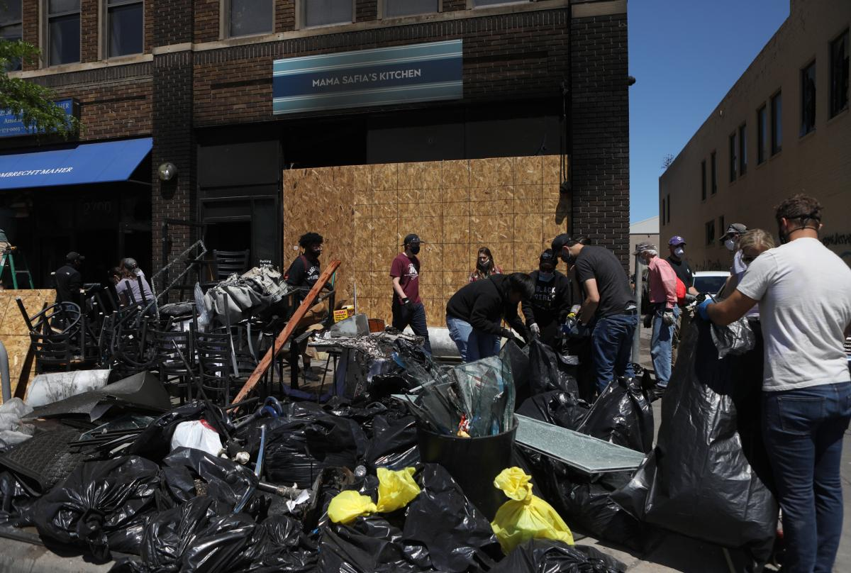 Volunteers clear debris from Mama Safia's Kitchen. Dozens of volunteers from across Minneapolis came to help.