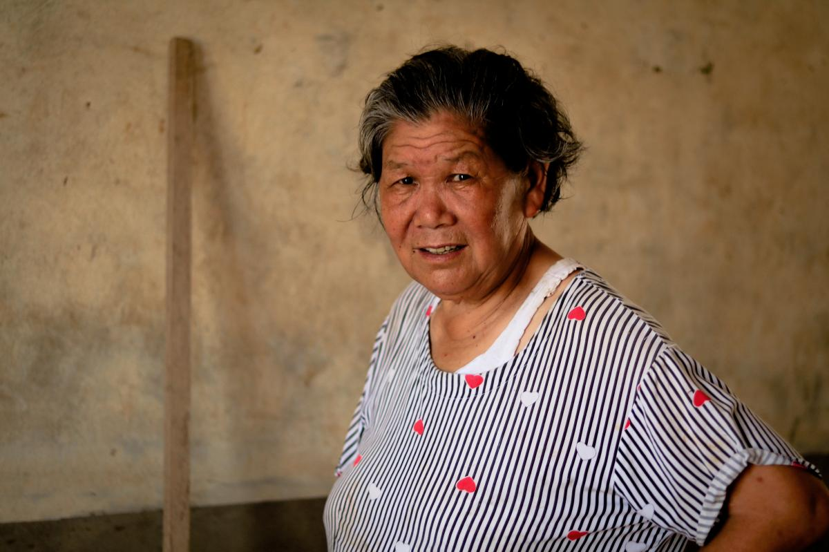 """Tang Anfeng, a Hekou native, explains how the local government releases excessive rainwater behind dams to relieve pressure. """"The water floods our village, and we suffer,"""" she said."""