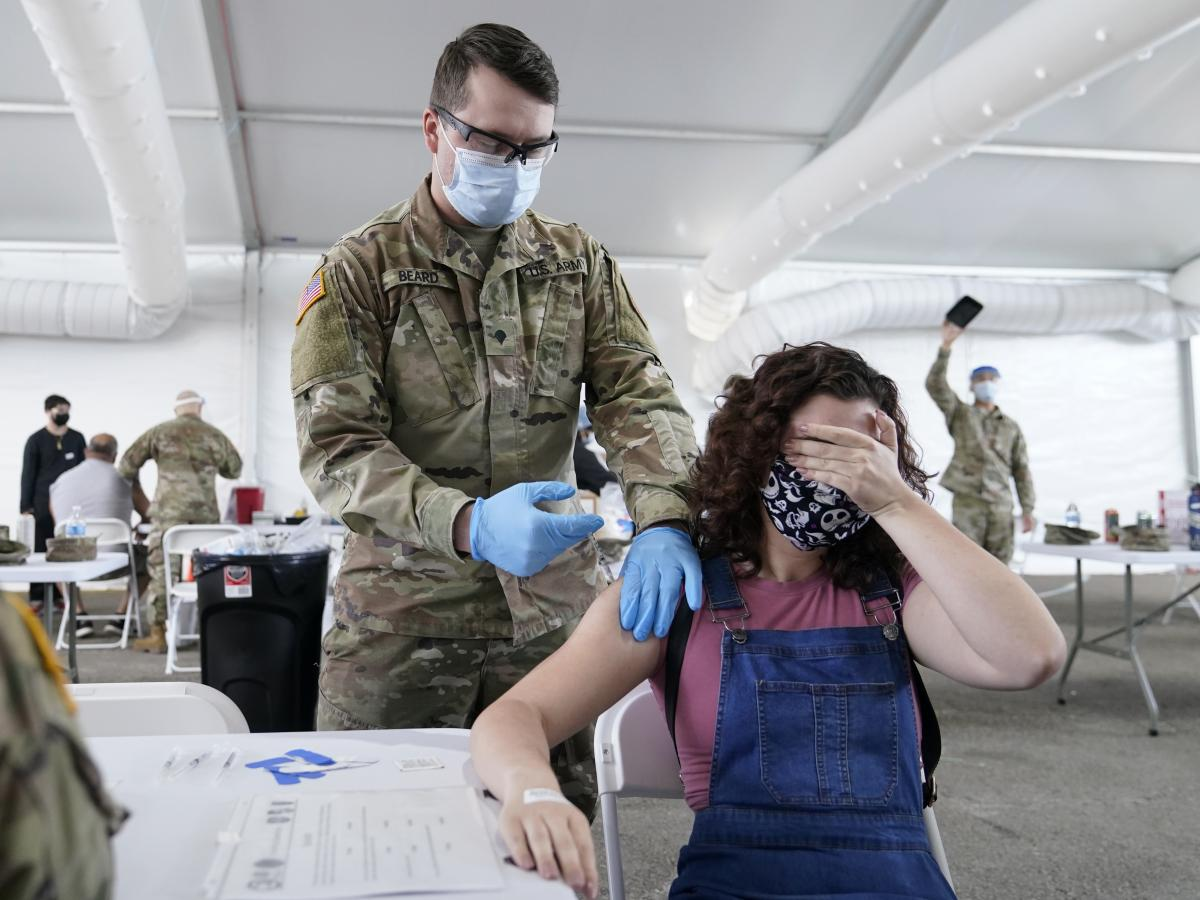 Leanne Montenegro, 21, covers her eyes as she receives a COVID-19 vaccine at a FEMA vaccination center in Miami in the spring. Months after multiple vaccines became available, some people are still not interested.