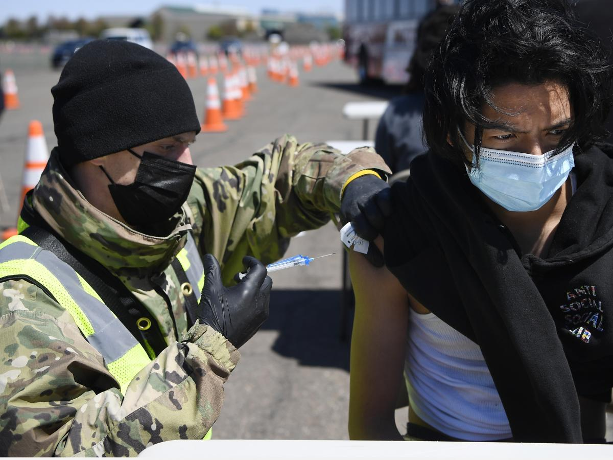 Connecticut National Guard medic Todd Smith administers a COVID-19 shot at a mass vaccination site in East Hartford, Conn. Rural hospitals suspect they may need help from federal agencies like the Guard if the vaccine mandate causes staff to leave.