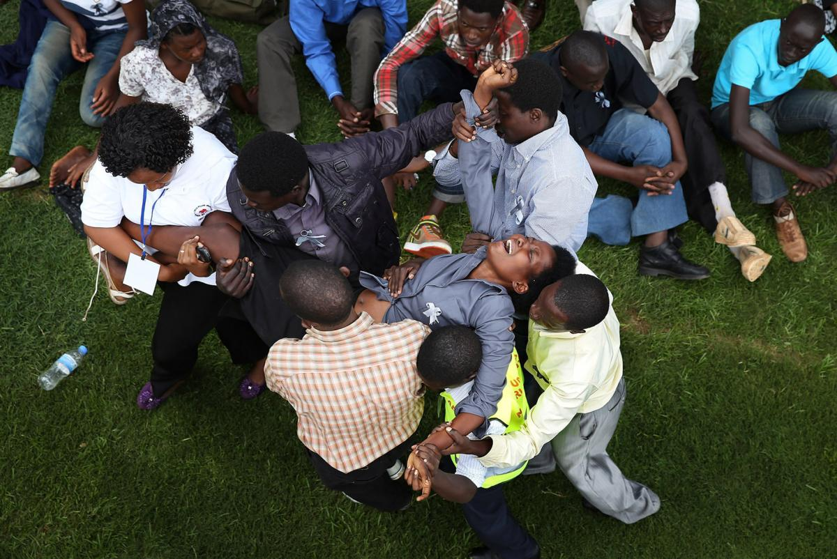 A distraught woman is carried out of Amahoro stadium in Kigali, Rwanda, on Monday during the 20th anniversary commemoration of the country's devastating 1994 genocide.