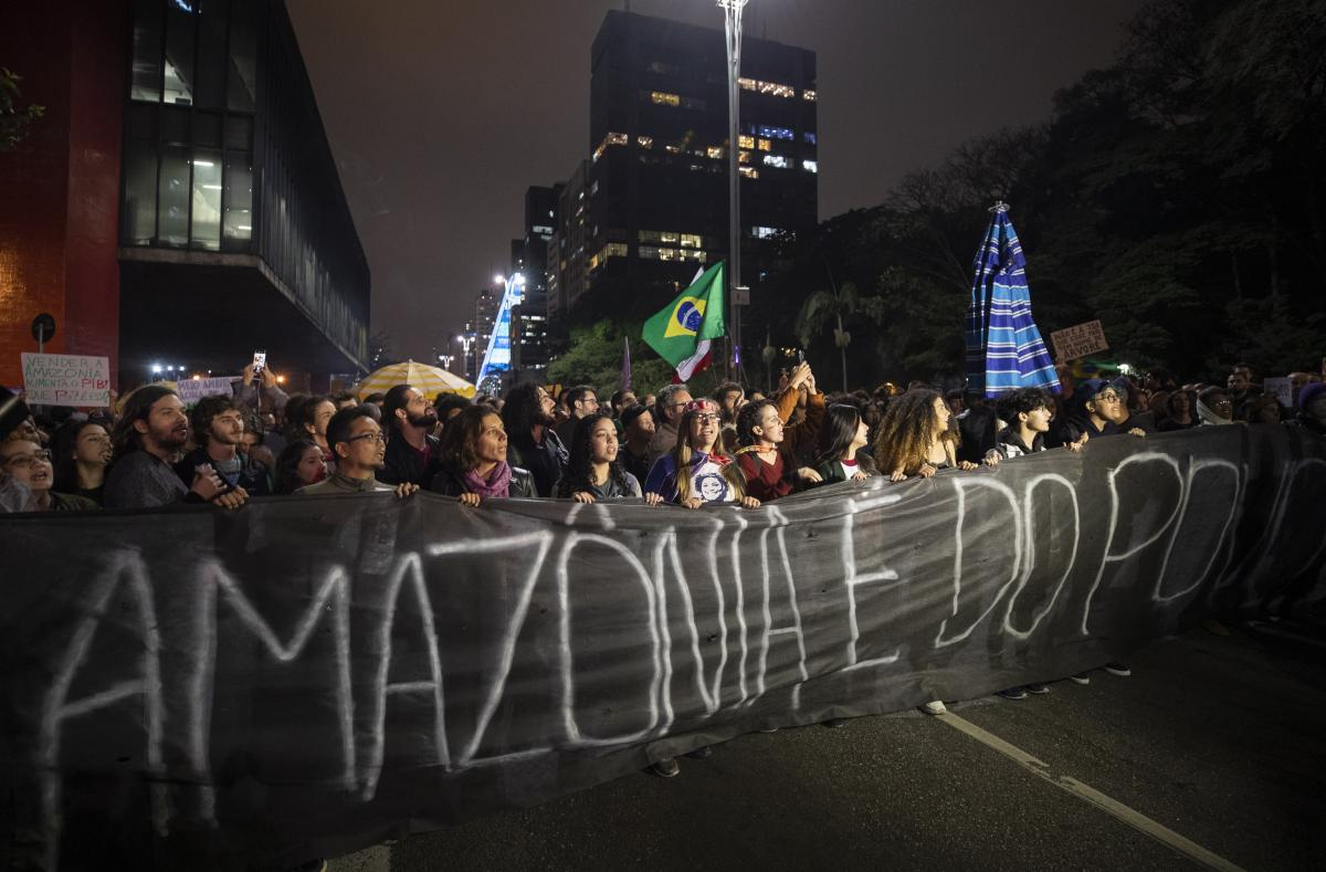 "Demonstrators march on Friday in São Paulo, Brazil, holding a banner with a message that reads in Portuguese: ""The Amazon belongs to the people."" Brazilians staged protests across the country throughout the weekend demanding action to combat the fires in"