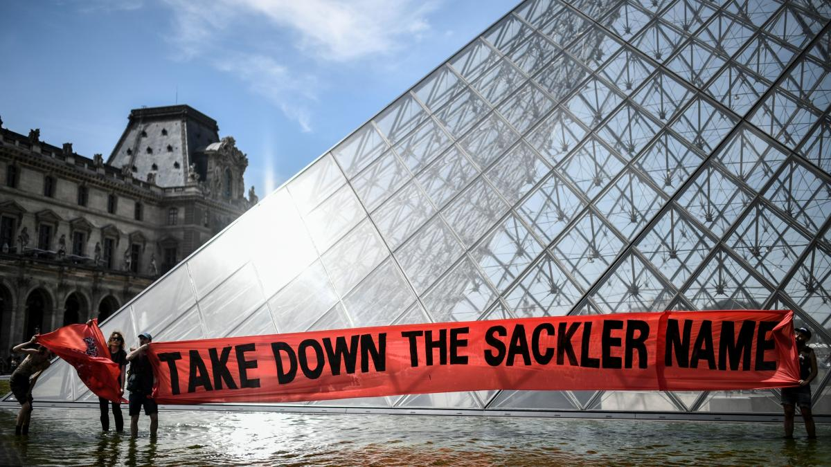 """Activists raise a banner reading """"Take down the Sackler name"""" during a demonstration earlier this year in front of the Louvre Pyramid in Paris."""