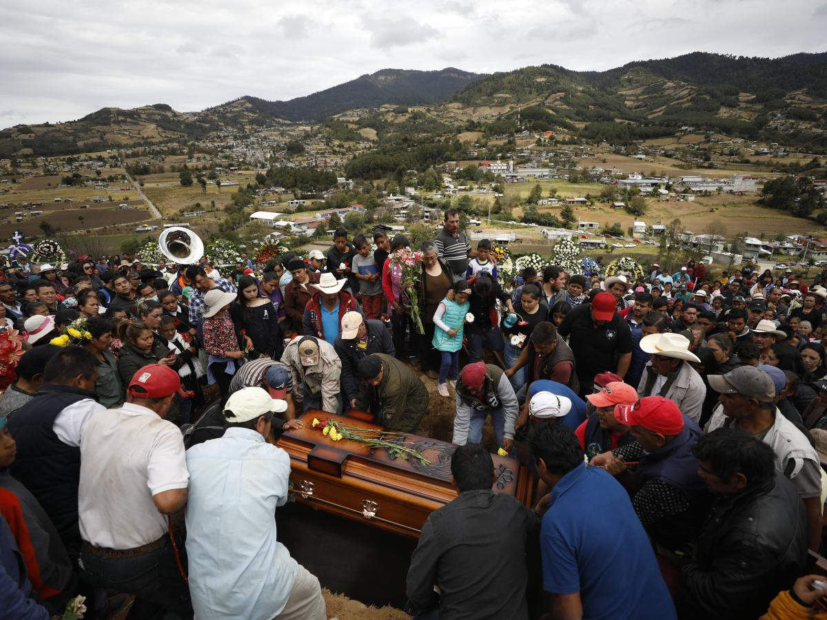 Mourners lower the coffin of community activist Homero Gómez González into a grave at a hillside cemetery in Ocampo, Mexico, on Friday.