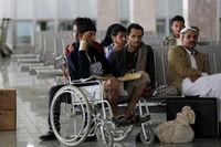 Yemeni men wounded during the airstrike at a funeral sit in the airport in Sanaa on Saturday as they wait for an Omani plane to evacuate them.