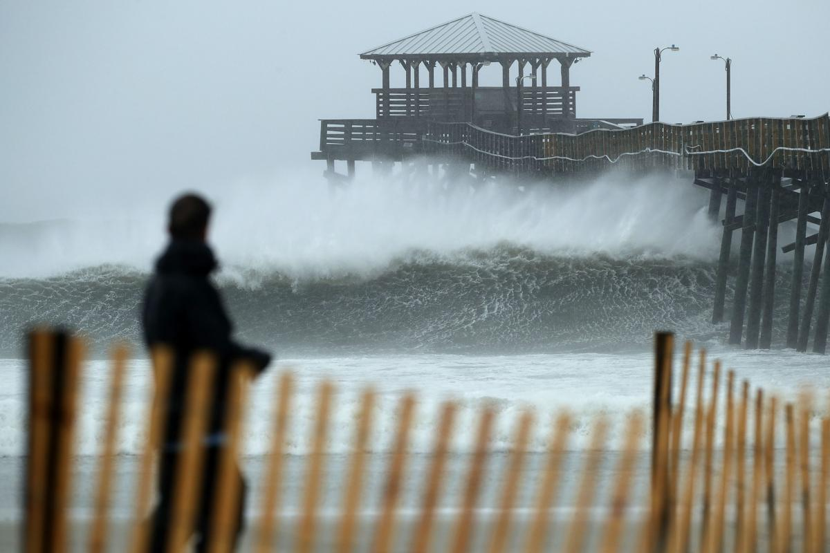 Waves crash underneath the Oceana Pier as the outer bands of Hurricane Florence begin to affect the coast on Thursday in Atlantic Beach, N.C. Coastal cities in North Carolina, South Carolina and Virginia are under evacuation orders as the Category 2 hurri