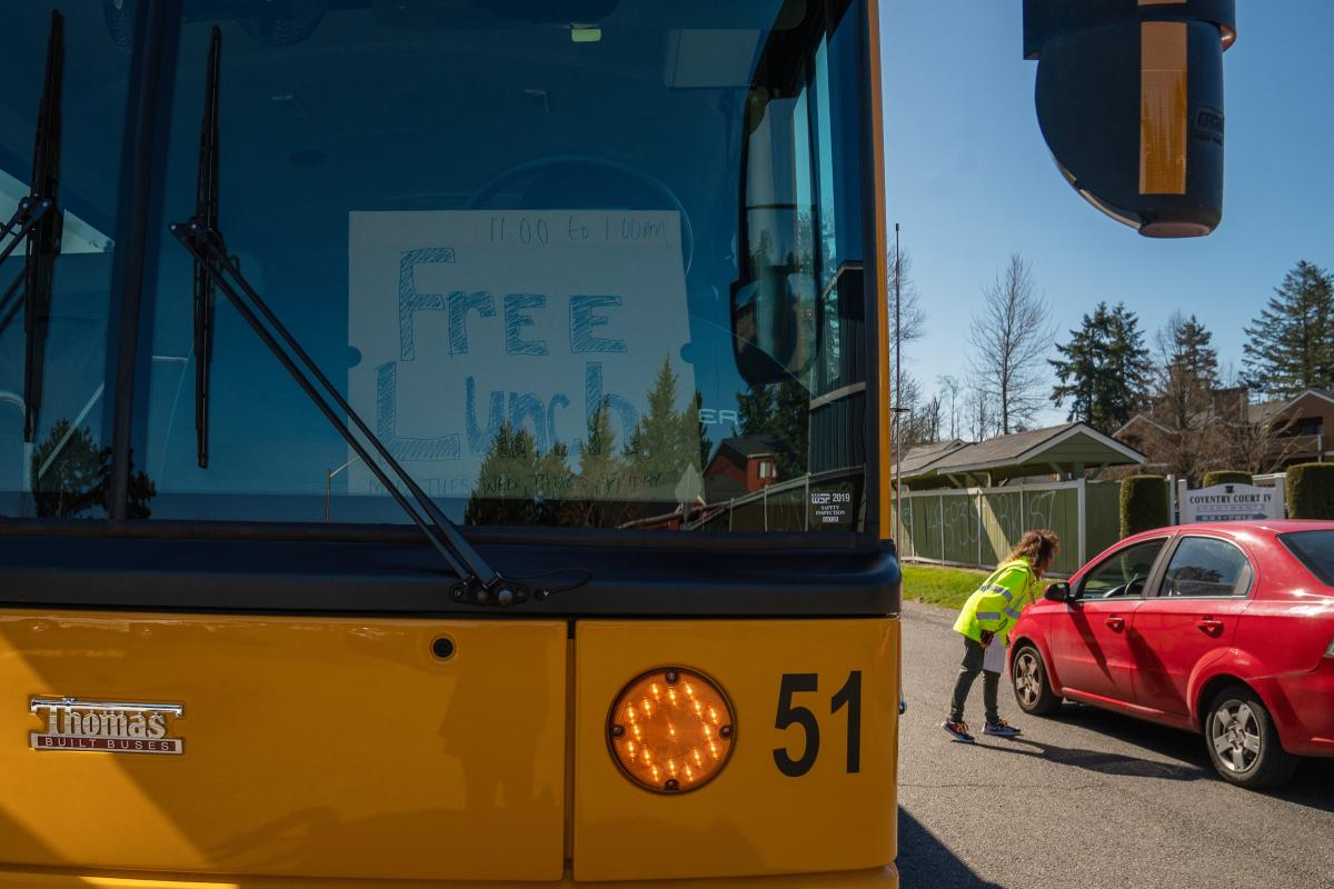 Franklin Pierce Schools bus driver Jennie Haws-Sebree stops a passing car at one of the district's meal distribution sites to inform the driver about the free lunch program. Despite phone calls and emails, few children knew about the program on its first