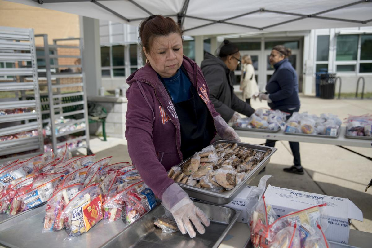 Jackie Nampha, a cafeteria worker at Washington-Liberty High School, helps with meal distribution in Arlington, Va.