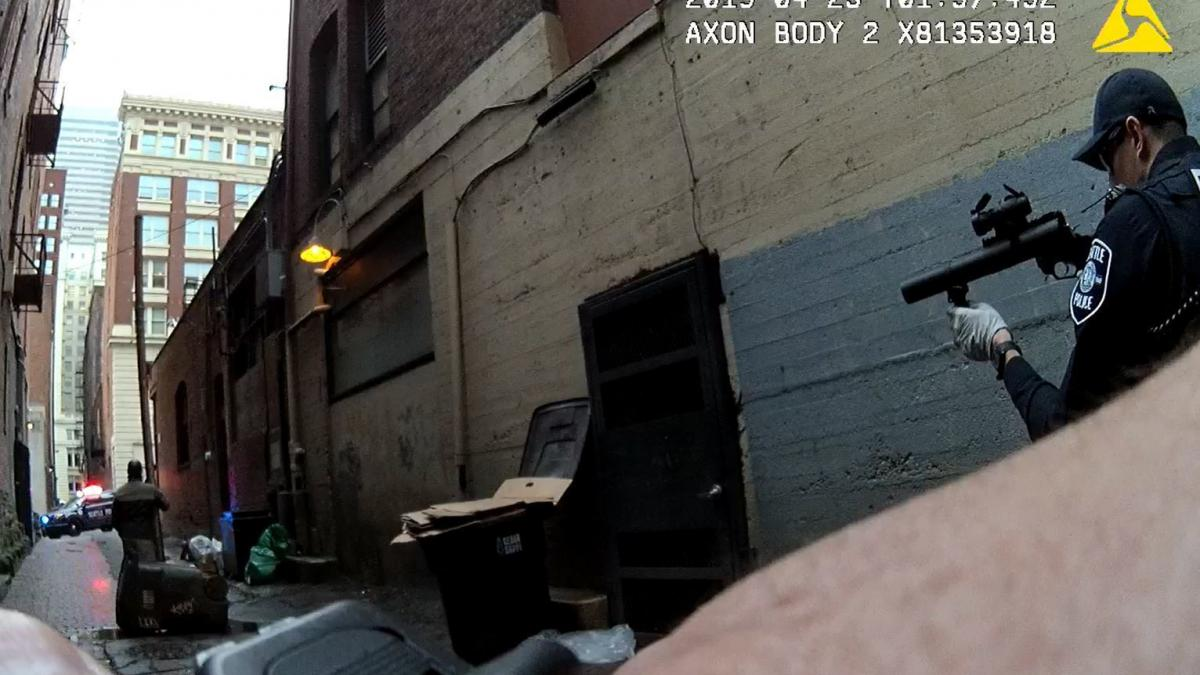Seattle Police in a standoff with a mentally ill man who has claimed an alleyway and has been chasing people out of it with a drainpipe. After nearly two hours of negotiations, he gave himself up.