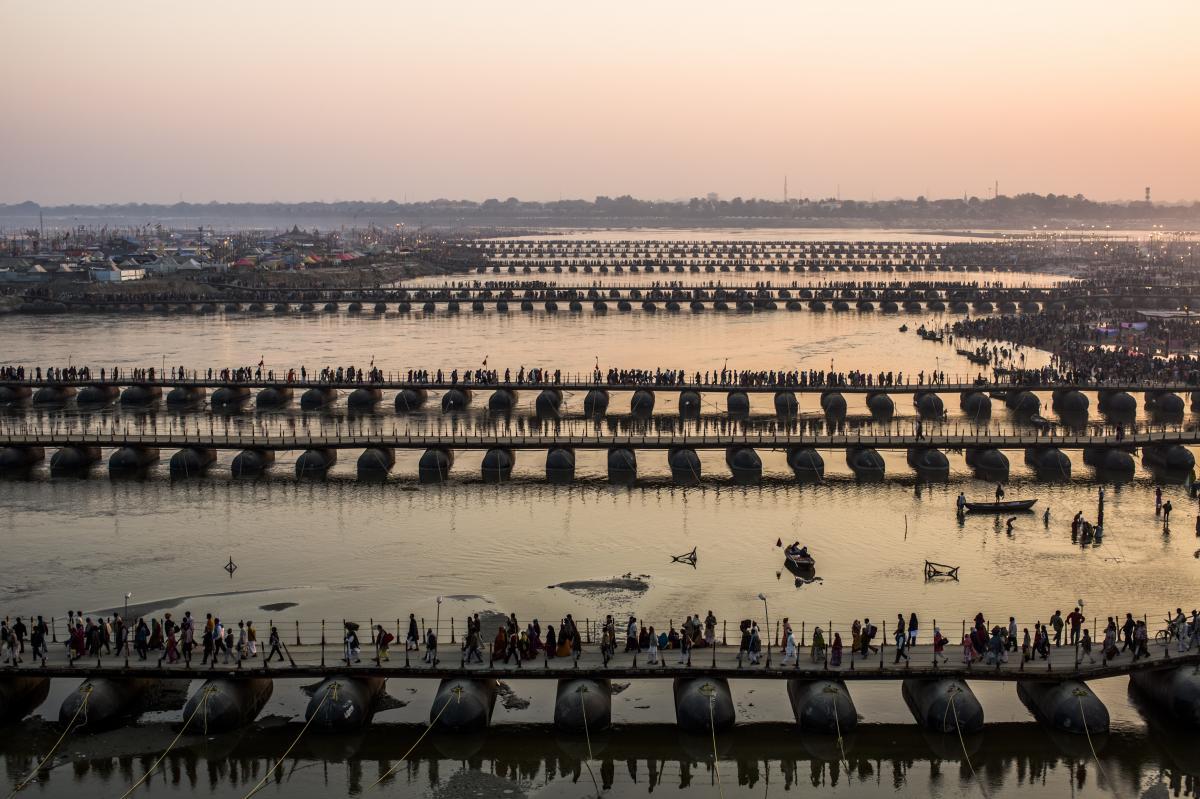 Pilgrims make their way over pontoon bridges.