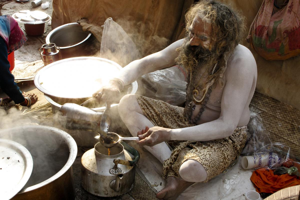 A naga sadhu smeared in ash serves up the early morning tea for his akhara, or sect, one of 13 that has its own camp on the 20-square-mile grounds.