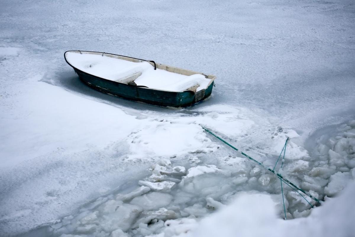 En ensom robåd sidder fast i isen i en havn i Nuuk.