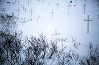Gravmarkeringer og nøgne buske begravet i sneen på en kirkegård i Nuuk.