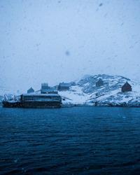 Kangeqs gamle anløbsbro og huse ser spøgelsesagtige ud under en snestorm sidst på vinteren.
